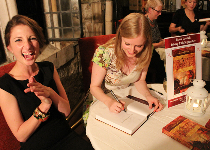 Lauren signing a copy of The Arrow of Sherwood